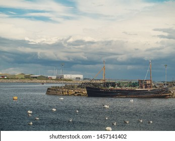 Old fishing boat and white swans colony, Claddagh, Galway city, Ireland, Cloudy sky.