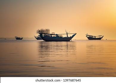 An old fishing boats at beach yellow sky background -Dammam Saudi Arabia