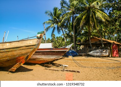 Old fishing boats on a beach with blue skys, palm trees and a beach house