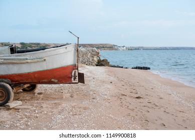 Old fishing boats on a sandy beach. Horizontal photo, no people.