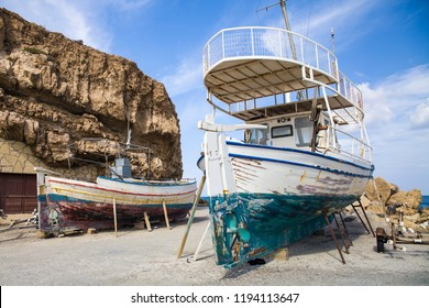 Old fishing boats on the shore. Ships pulled ashore. Harbor in the village of Hersonissos on the island of Crete, Greece.
