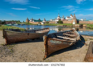 Old fishing boats on the shore against the background of the Transfiguration of the Solovetsky Monastery. Solovki, Russia
