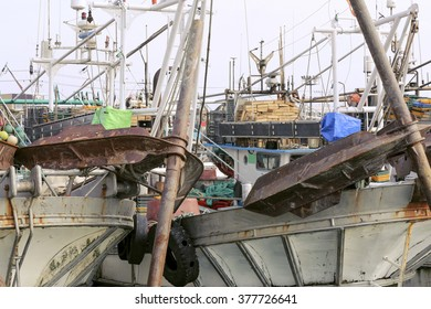 Old fishing boats waiting in a harbor to go out and troll nets.