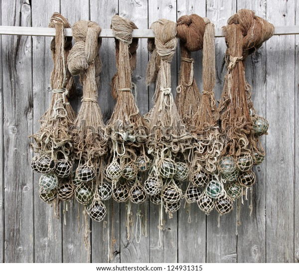 Old fishing nets with glass floats hanging at a boathouse wall in Norway.