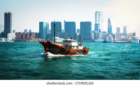 Old fishing ship with skyscrapers of Hong Kong in the background. Cityscape of Hong Kong. Urban skyline