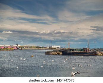 Old fishing ship and white swans colony, Claddagh, Galway city, Ireland, Cloudy sky.