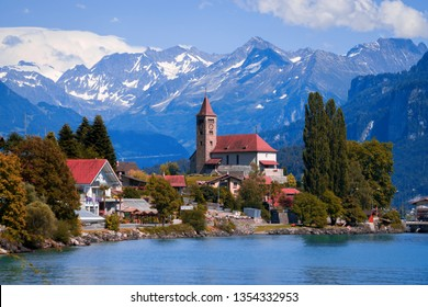 Old fishing town with beautiful church and fabulous snow covered Alps mountains on background. Panoramic view on Brienz town on lake Brienz by Interlaken, Switzerland. Switzerland, Bohemia, Europe.