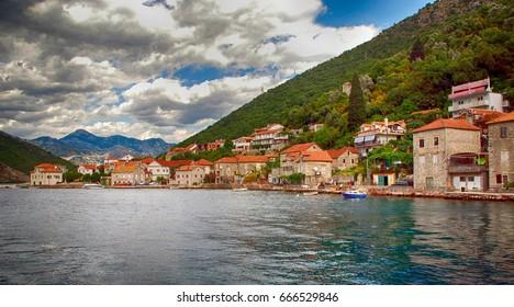 Old fishing village with traditional mediterranean stone houses in the Kotor Bay(Boka Kotorska), Montenegro. Panoramic view, dramatic sky