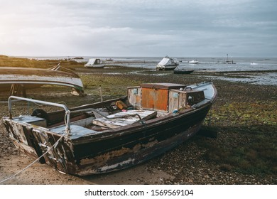 Old flaked fishing boat with a small cabin inside on the shallows on a forsaken pier in a wasteland; a horizon, waterscape, and more several boats behind in a defocused background, Alcochete, Portugal