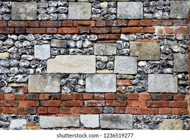An old flint, stone and brick wall in the grounds of Winchester cathedral, Hampshire, UK.