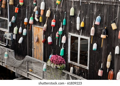 Old floats hanging on the wooden wall of restaurant as decoration in Bar Harbor, Maine, USA