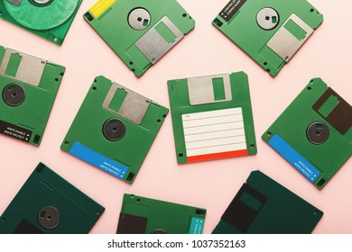 Old floppy disks isolated on pink background. Top view of magnetic retro storage devices, cutout of green diskettes, copy space, flat lay