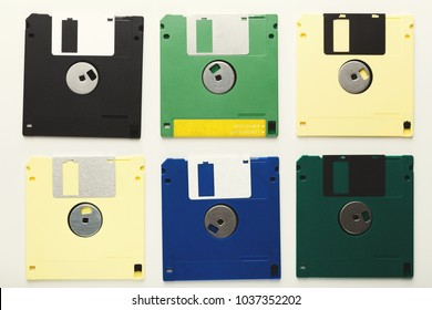 Old floppy disks isolated on white background. Top view of magnetic retro storage devices, cutout of colorful diskettes, copy space, flat lay