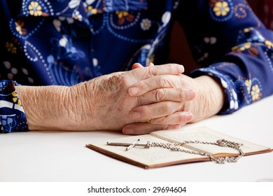 Old folded hands in front of a book and cross.  Focus on the hands.
