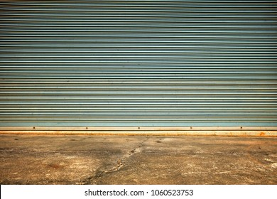 Old Folding Metal Door with Concrete Pavement.