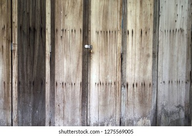 An old folding wooden door showing raw and unpainted textured patterns is closed with a saftey lock in vintage style