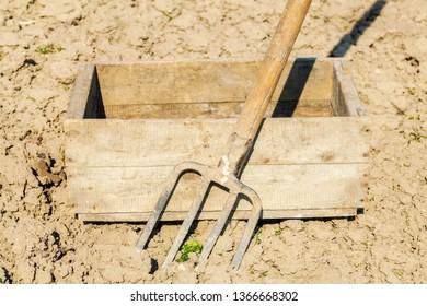 Old fork near wooden box on field