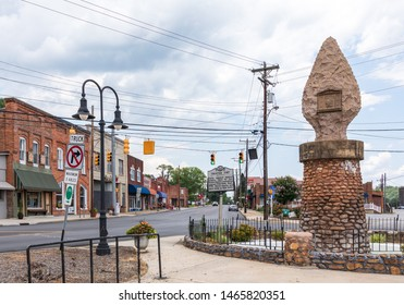 OLD FORT, NC, USA-27 JULY 2019: A monument stands on a corner of Main St., documenting the old Appalachian Indian Road, and a sign describes a frontier fort formerly at that location.