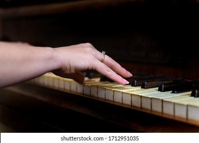 Old forte piano with female woman hand and diamond ring finger pianist playing closeup for concert with black background