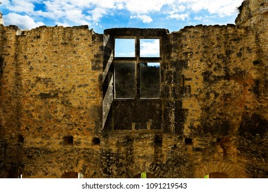Old fortified wall with windows. Ancient ruins in southwestern France.