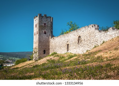 Old fortress Caffa in Feodosia, Crimea, Russia. Panorama of the Genoese fortress ruins on the Southern coast of Crimea in summer. It is a landmark of Crimea. Scenic view of a medieval tower and wall.
