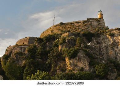 The Old Fortress of Corfu's Castle Near The Land Peak with its cross and the lighthouse, Kerkyra, Corfu Island, Greece, Europe The Old Fortress of Corfu is a Venetian fortress in the city of Corfu.