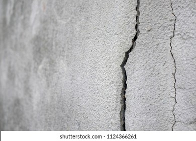 Old foundation and plaster wall with cracks. Building requiring repair closeup.