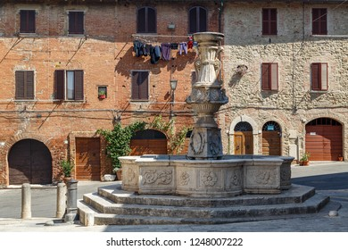 Old fountain in Asciano town, Italy