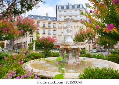 Old fountain and colorful flowers in the middle of the Place Francois 1er, Paris, France