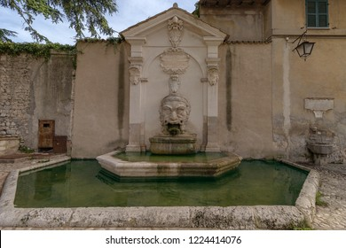 Old fountain (Fontana del Mascherone) on the wall of the thirteenth-century former church of Saints Simon and Jude in  Spoleto, Umbria, Italy
