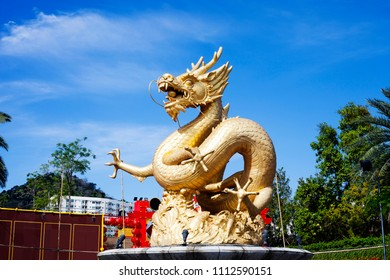 Old fountain with gold Dragon in Phuket Town, Thailand. Golden chinese Sea Dragon sculpture on city street