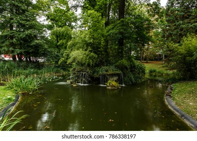 Old Fountain in the Summer Park of Western Europe. Green bushes and trees. Lake and blurred water.