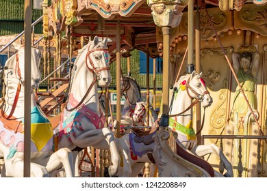 Old French carousel in a holiday park. Two horses on a traditional fairground vintage carousel. Merry-go-round with horses and music. Sunny day.