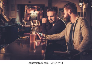 Old friends drinking draft beer at bar counter in pub