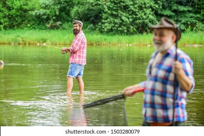 old friends. family bonding. summer weekend. two fishermen with fishing rods, selective focus. mature man fisher. hobby and sport activity. son and father fishing. male friendship.