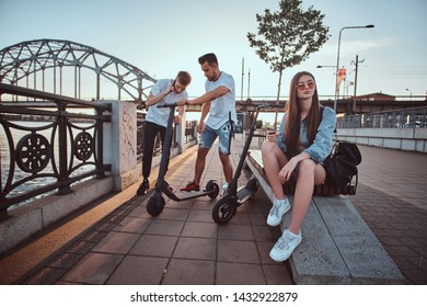 Old friends meet up at riverside, one of them is speaking by mobile phone, another have a scooter, girl is sitting on the bench.