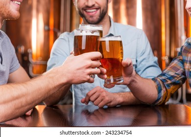Old friends meeting. Close-up of three happy young men in casual wear toasting with beer while sitting in beer pub together