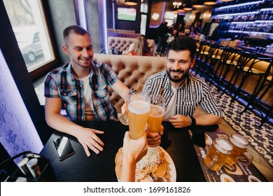 Old friends meeting. Three cheerful young men drinking beer in bar