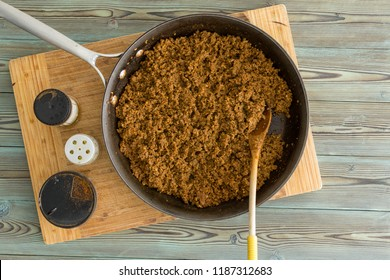Old frying pan filled with savory seasoned cooked ground beef for sloppy joe tacos alongside assorted condiments in an overhead view on a wooden board on a kitchen table