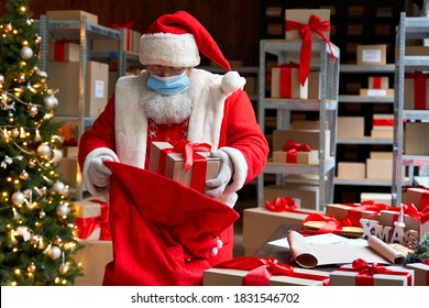Old funny bearded Santa Claus wearing costume, face mask, packing presents gift boxes in sack bag preparing for xmas eve in workshop. Merry Christmas Covid 19 coronavirus safe delivery concept.