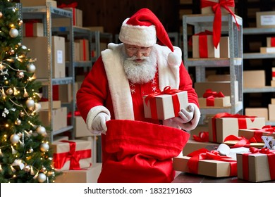Old funny Santa Claus, Saint Nicholas packing presents gift boxes in sack bag preparing post shipping fast xmas delivery parcels standing in workshop. Merry Christmas shipping delivery concept.