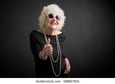 Old and funny woman holding thumbs up