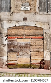 An old garage door made of many pieces of wood has endured centuries of weather on Rue Maziere in the town of Beaune in the Burgundy region of France.