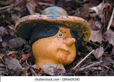An old garden figure with head carved among brown dry autumn leaves
