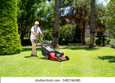 Old gardener with lawn mower in green garden