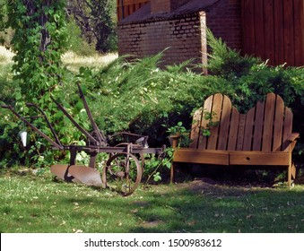 An old gardening plow sits next to a beautiful wooden bench in front of a grandmother's home in rural California