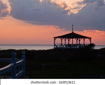 An old gazebo is silhouetted against a purple-red sunset sky.
