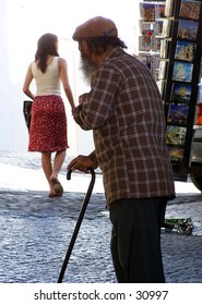 Old geezer with cane oogling young woman in streets of Lisbon, Portugal
