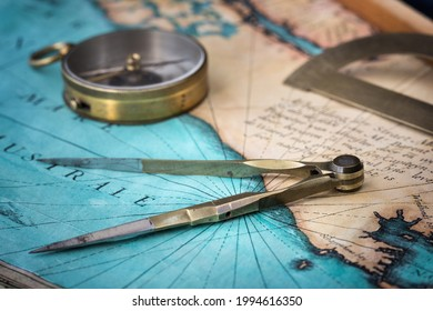 An old geographic map with navigational tools: compass, divider, protractor. View of the workplace of ship's captain. Travel, geography, navigation, tourism, history and exploration concept background