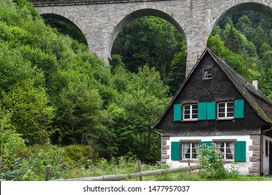 old German house with green shutters by old train trestle in Black Forest mountains
